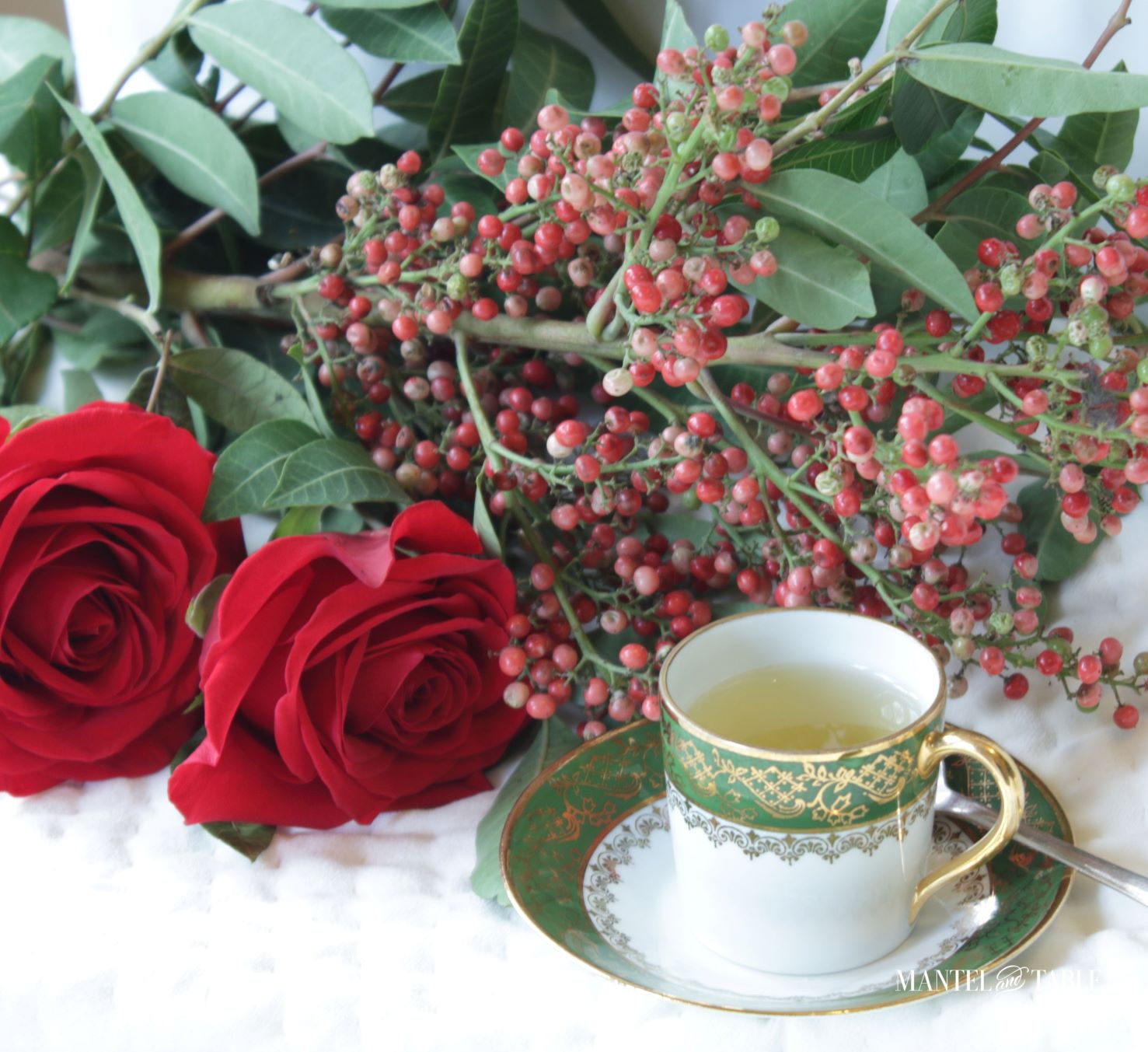 Green and gold teacup with red roses on quilted white
