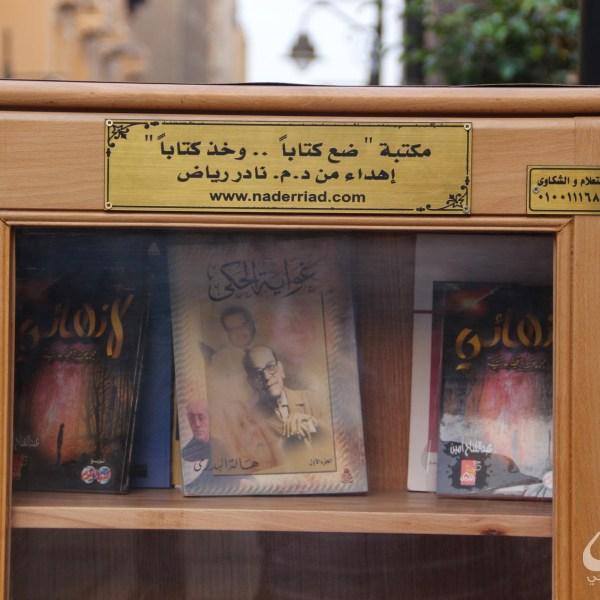 """كتب على المكتبة: """"مكتبة ضع كتابًا..وخذ كتابًا.. إهداء من د. م. نادر رياض"""