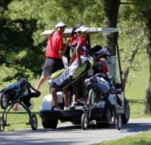 The girl's hopped onto the golf cart as Mr. Barr drives them to the first hole. Photo by Lisa Pham