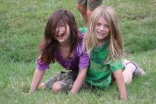 Children play tag, and wrestle in the open field at Irish Festival.
