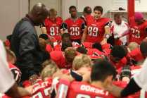 Football Coach, Oliver Lucas, prays with his team before the game