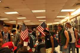 The seniors process in from the parking lot in the morning, carrying American flags and wearing the colors to match. Photo by Cara Jennings
