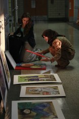 Maha Jabbar (12) gazes at Eldina Preljevic's (12) art pieces that she laid out in the hallway.