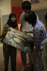 Maha Jabbar (12) and Bowen Sung (12) watches as Jennifer Bui (12) pulls out her artwork.