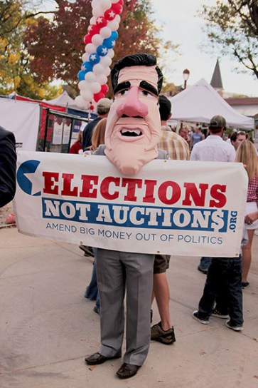 Some protesters used mascot-style masks of both Mitt Romney and Barack Obama to help with their point about money in politics.