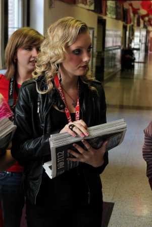 Molly Loehr (11) passes out newspapers around the school during Costume Day for Red/White Week. Photo by Mesa Serikali