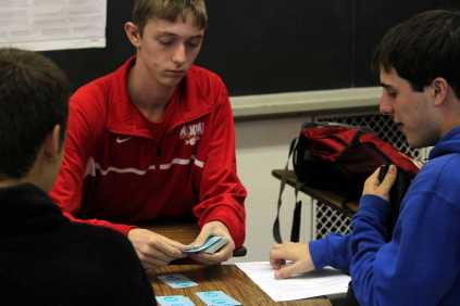 Austin Snider (11) deals the cards to start a game to pas time until the bell rings.