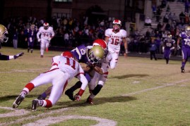 Justice Lucas (11) and Micheal Nelson (12) tackle a Male player with the ball.