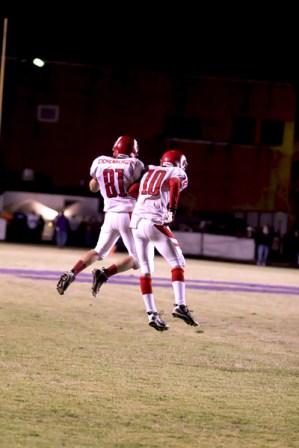 Daylen Eichenberger (10) and Mason Motley (11) jump into the air after a crimson touchdown.
