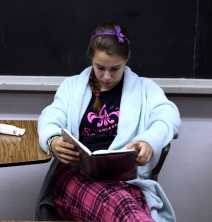 Phebe Ligon (11) calms herself by opening a book after she takes the PSAT. Photo by Molly Loehr