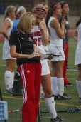 Coach Brittany Tolan talks strategy to Cara Jennings (11, #35) before Jennings entered the game. Photo by Kinsey Ball