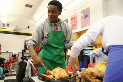 Mikel Jordan (12) carve the turkey for the dinner. Photo by Jacqueline Leachman