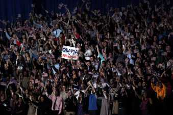The crowd behind the stage stands and cheers, awaiting for the president's victory speech.