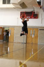 Tim Comstock (9) goes to dunk just making it in the basket during warm ups.