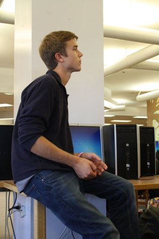 Logan Fairfield (11) sits on computer table after coming in late and not having a seat.