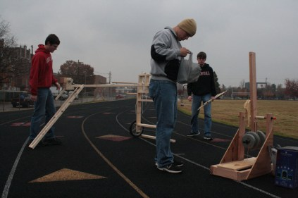 Students of Mr. Garrett's Global Issues class assemble their homemade weapons before testing them out on the practice field.