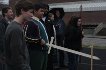 Students of Mr. Garrett's Global Issues class watch their peers test out their homemade weapons. Omar Mostafa (11) holds the sword he brought in for the project.