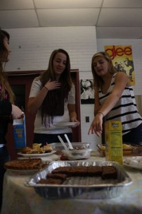Meredith Bell (12), explains all the different food on the table, to Kelsi Embry (11) and Courtnee Hall (11).