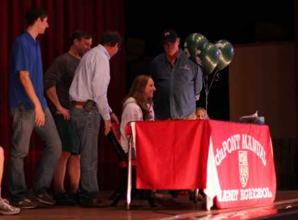 Sarah Love, (12) signs her letter of intent to swim at Michigan State University.
