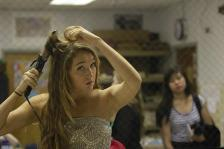 Catherine Anderson (12) curls her hair by looking at the reflection in the mirror.