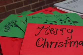 The finished cards pile up on the table to later be distributed to children in hospitals.
