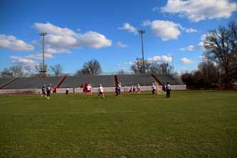 The clouds part to shine sunlight on the field as Manual's Varsity Lacrosse team defends against Male.