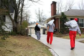 Members of the team walk up to the back of the house to drop the bags off.