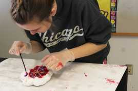 Student works carefully on tie-dye t-shirt design.