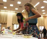 Two NHS volunteers, Christina Rucinski (11) and Martha Gottbrath (11) set up the refreshment table.