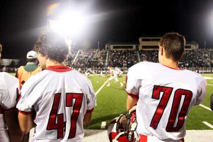 Joe Tisone (#47) and #70 watch from the sidelines as the Trinity VS. Manual game begins.