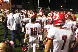 Manual's varsity football players follow their coaches as haftime ensues.