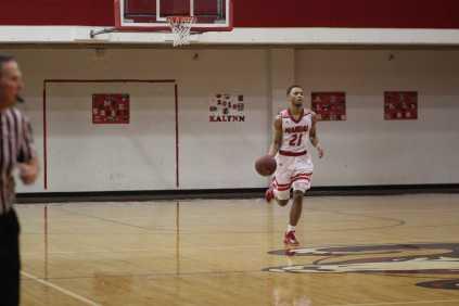 Jordan McClendon (#21, 12) dribbling down the court. Photo by Jade Broderick