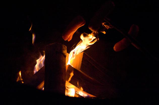 Würste über dem Feuer bei Nacht