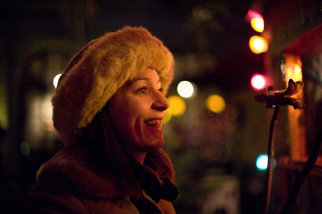 Lachende Frau mit Weihnachtsbeleuchtung im Hintergrund