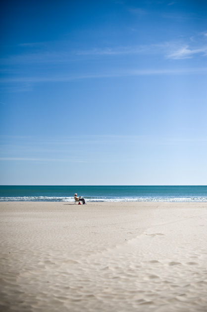 Alte Frau auf dem Liegestuhl beim Lesen am Strand