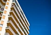 Hochhaus mit Kondensstreifen vor blauem Himmel
