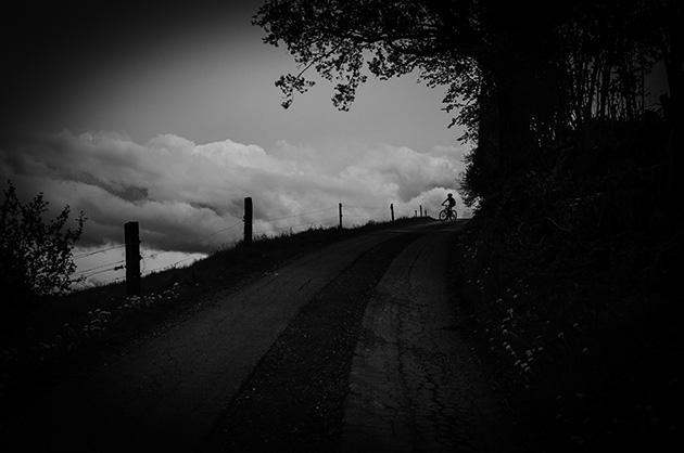 Landschafts-Fotografie – Bild von einem Jungen auf einem Fahrrad im Gegenlicht. Im Hintergrund Wolkenbilder.