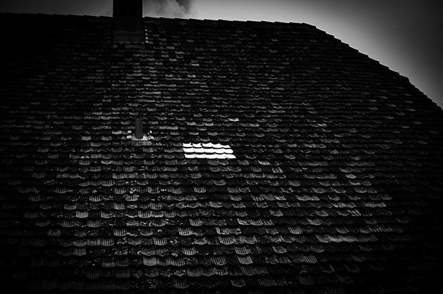 Glasziegel reflektieren das Sonnenlicht auf einem Hausdach in Gurten-Kulm