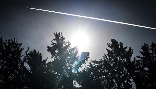 Fotografie – ein Mitbringsel aus unseren Ferien. Aufnahme im Gegenlicht mit einem Wald, einem Gleitschirm und einem Kondensstreifen eines Flugzeuges am Himmel.