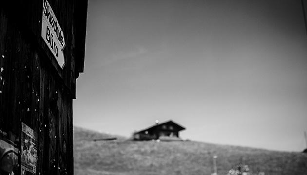Beitragsbild – Schild «Skischule und Büro», das auf ein Haus auf einem Hügel im Hintergrund zeigt.