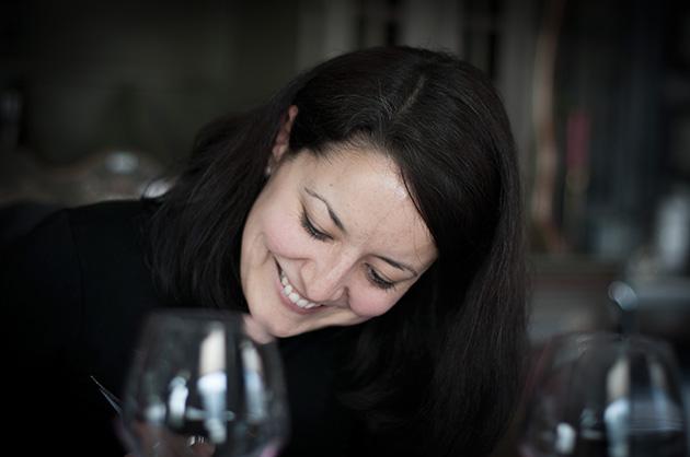 Lächelnde Frau mit gesenktem Blick auf einen Tisch