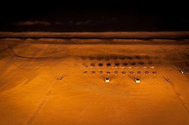 Nachtaufnahme von einer Dachterrasse auf den Strand mit Sonnenschirmen und den zusammengestellten Liegestühlen. Im oberen Bildbereich schwarz das Wasser des Meeres.