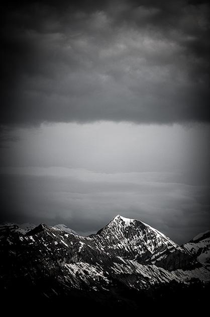 Sonnenschein auf einer Bergspitze, darum Regenwolken