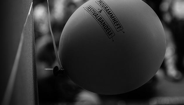 Dokumentations-Fotografie vom Buskers in Bern. Beitragsbildmit einem angeschnürten Ballon in einer Berner Sandstein-Laube