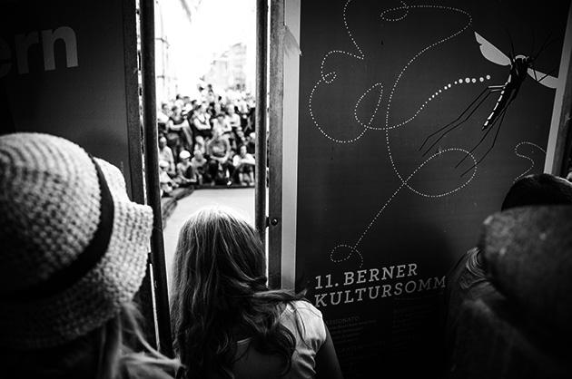 Buskers – Zuschauer schauen durch einen Spalt zwiaschen zwei Plakat-Stellern