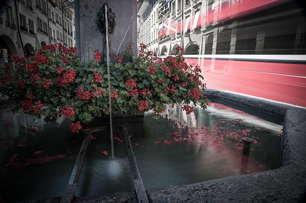 Langzeitbelichtung bei Tag, Brunnen mit einem vorbeifahrenden Trolley-Bus