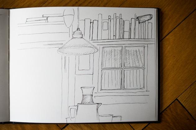 Zimmerdetail mit Fenster, Lampe und Büchern im Innenraum eines alten Bauernhauses