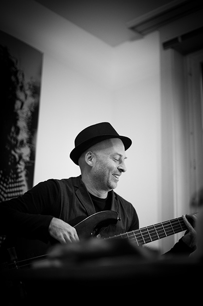 Wolfang Zwiauer spielt auf einer Bassgitarre – Schwarz-Weiss-Portrait