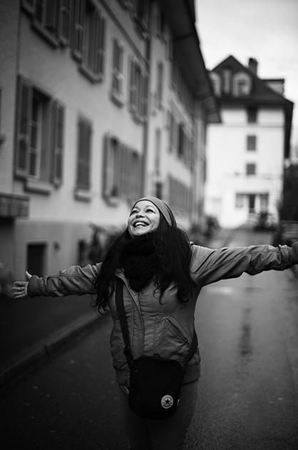 Eine Frau lacht und streckt die Arme aus, Foto aufgenommen in der Muristrasse für das Murifeldbuch
