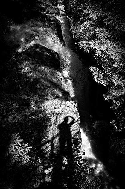 Silhouette eines Fotografen auf dem Boden in der Nähe eines Wildbachs auf der Griesalp.